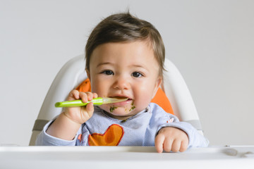 Baby Boy Eating with Spoon in High Chair, Studio Shot