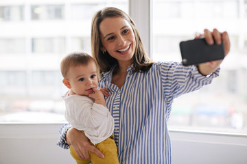 Young mother taking a selfie with her baby at home.