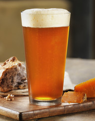 Glass of Beer with Bread and Cheese on Breadboard, Studio Shot