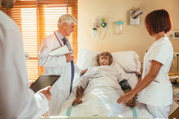 Medical staff attending a patient on bed