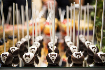 Close-up of Chocolate Tuxedo Lollipops on Dessert Table