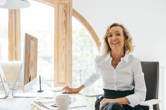 Smiling mature businesswoman working at office.