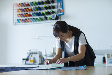 one asian female tailor working in studio