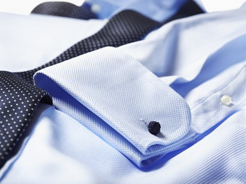 Detail of cuff of blue shirt with tie over in studio
