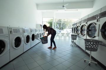 Woman using washing machine at laundromat