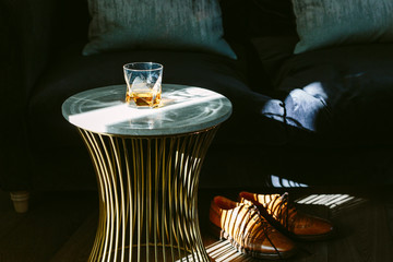 The end of the week. A glass of whisky, a neck tie and brown brogue shoes in a modern room setting. Dramatic lighting.