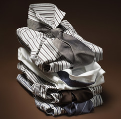 Stack of men's, striped dress shirts with ties on brown background