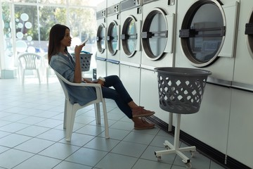 Woman talking on phone while waiting at laundromat