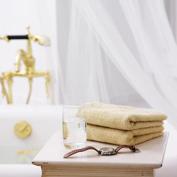 Side Table in Bathroom with Towels, Glass of Water and Watch