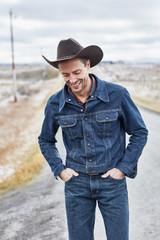 Cowboy in denim walking down the road
