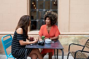 Trendy girls having drinks outside