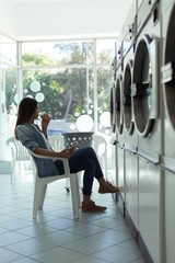 Woman having coffee while waiting at laundromat