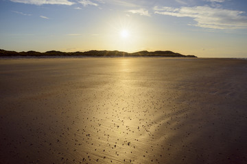 Sun reflecting on the sandy beach at low tide on the North Sea at sunrise, Bamburgh in Northumberland, England, United Kingdom