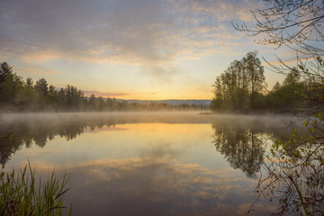 Pastel sky reflected in lake with morning mist at dawn in Mondfeld, Wertheim in Baden-Wurttemberg, Germany