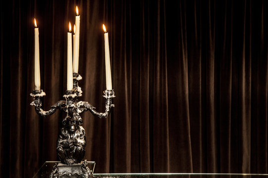 silver candle holder.with candles lit on a table.