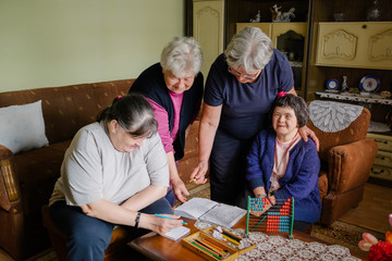 Two senior female friends having educational time with caregiver