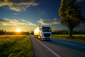 Fotobehang - Truck driving on the asphalt road in rural landscape at the golden sunset