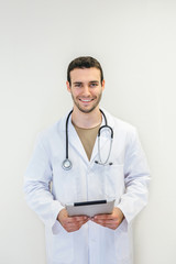 Cheerful young doctor man with tablet