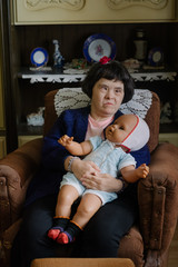 Portrait of a female model with down's syndrome holding her doll
