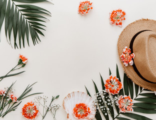flat lay blogger background with tropical leaves, hipster hat,  accessory and flowers on pastel background