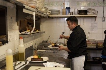 Male chef serving food in a plate
