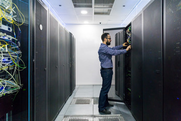 Technician performing maintenance tasks in a server room rack