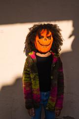 Scary girl in pumpkin head in sunlight