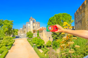 Tourism and travel concept in Europe.Mobile phone with Portugal flag cover taking photos of tourist attractions in city of Knights Templar. Church of Convent of Christ on blurred background.Copy space