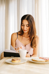 Woman having breakfast and writing