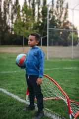 Little boy having fun learning soccer skills outside