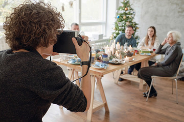 Woman capturing Christmas family dinner