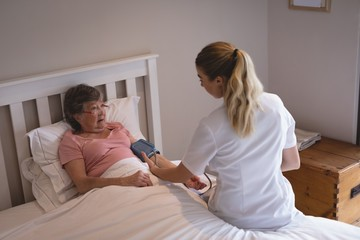 Physiotherapist checking blood pressure of senior woman