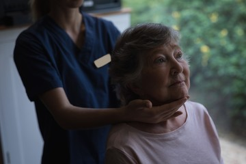 Physiotherapist giving a neck massage to senior woman