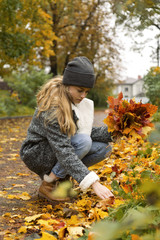 Woman collecting autumn leaves