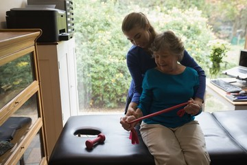 Physiotherapist assisting a senior woman to stretch an elastic