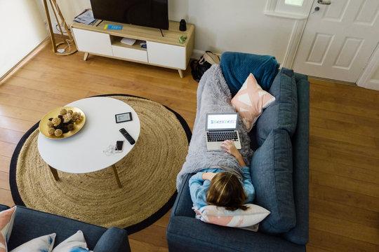 overhead view of teenager on sofa