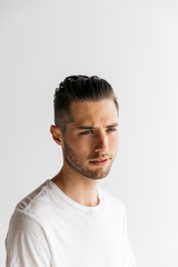 Head shot portrait of young adult male with short hair wearing white t-shirt in studio