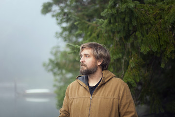 Man in hooded jacket stands on a dock in Fletcher Bay on a foggy morning.