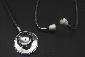 Medical stethoscope on blackboard.