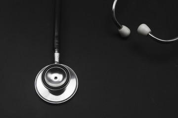 Medical stethoscope on blackboard.