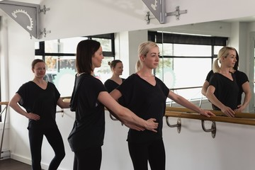 Trainer assisting young woman stretching on barre