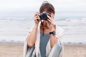 Young stylish beautiful and sensual brunette woman photographer are making pictures on the beach near the sea, smiling, having fun, looking fashion style