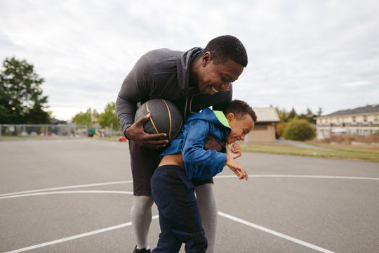 Dad and son having fun on outdoor basketball court together