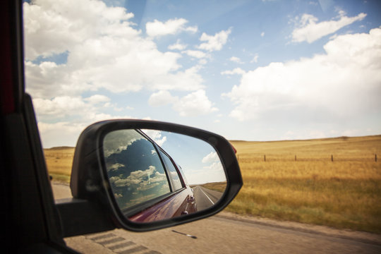 Reflection of sky and clouds in car passenger side window