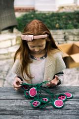 Sukkot: Girl Works To Untangle Watermelon Garland