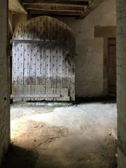 Old wooden door opened into rural barn.