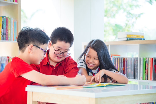 Young asian students reading book in school library