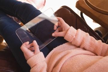 Girl using glass digital tablet in living room
