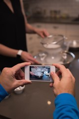 Person photographing woman while cooking food in kitchen