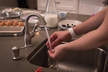 Woman washing her hands in kitchen